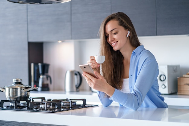 Young happy woman using smartphone and wireless headphones for reading audio book during coffee break in the kitchen at home. modern mobile people