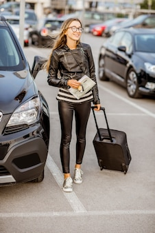 Young and happy woman walking with suitcase holding rental contract on the car parking