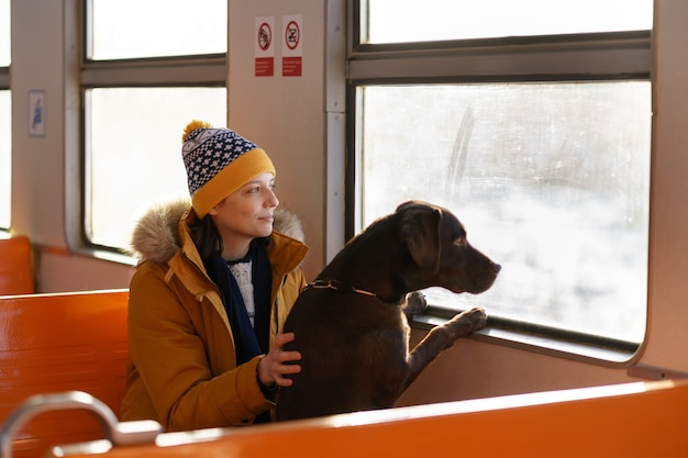 Young happy woman wear winter clothes sitting in local train with her lovely dog, hugging, thinking, looking through the window, traveling together. love pets.