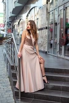 街を歩いているイブニングドレスを着た若い幸せな女性。夏時間