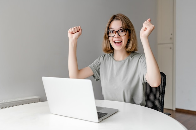 Young happy woman wearing glasses winning the prize sitting with laptop in the apartment