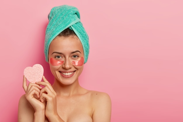Young happy woman wears collagen moisturizing patches under eyes, holds sponge for removing makeup, has beauty treatments, has fresh skin after taking shower