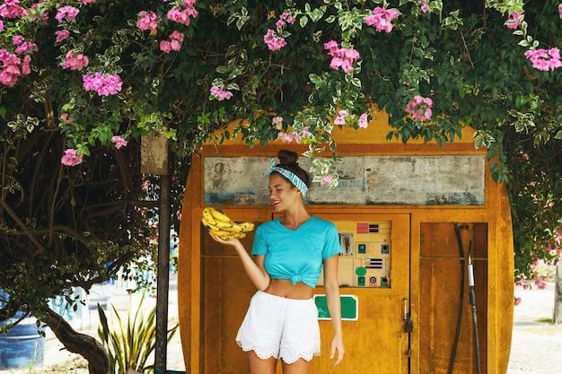 Молодая счастливая женщина с кучей бананов позирует возле старой заправочной станции