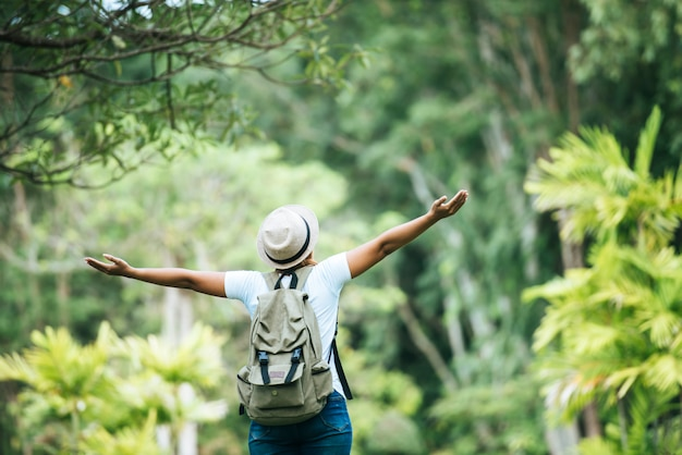 Young happy woman with backpack raising hand enjoy with nature.