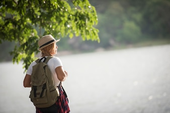 Young happy woman with backpack standing looking to the river. Woman traveling concept.