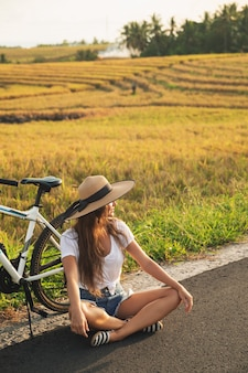Young and happy woman with a bicycle on side of the road