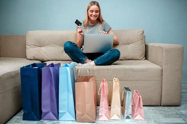 신용 카드를 가진 젊은 행복 한 여자는 쇼핑백과 함께 소파에 앉아있는 동안 온라인 상점에서 큰 판매를 준비