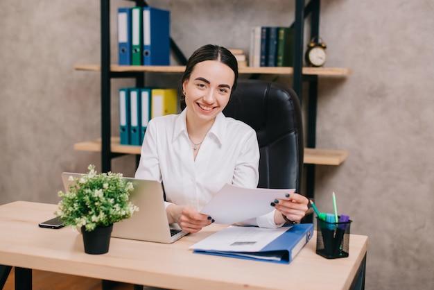 Officeのドキュメントを持つ若い幸せな女