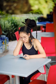 テーブルに座っている間彼女のタブレットから読んでドレッドヘアを持つ若い幸せな女性4