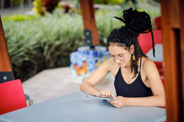 テーブルに座っている間彼女のタブレットから読んでドレッドヘアを持つ若い幸せな女性。