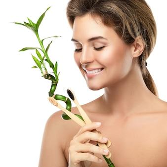 環境に優しい竹の歯ブラシを持つ若い幸せな女性