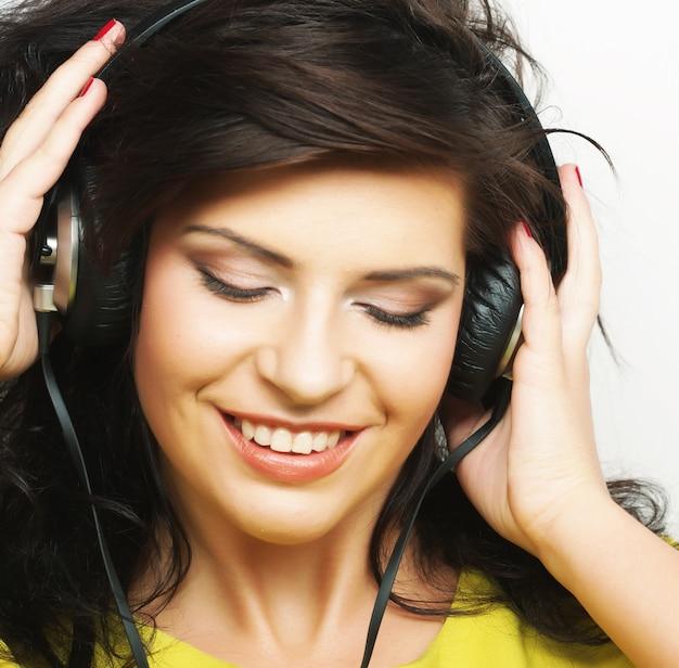 Молодая счастливая женщина с наушниками, слушающая музыку