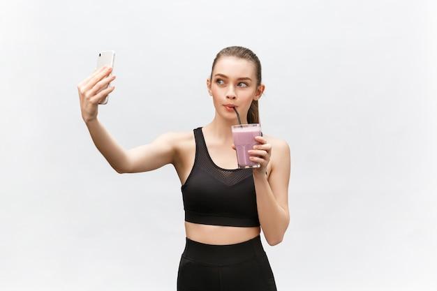 Молодая счастливая женщина с питьевой встряхивания здоровой диеты для спорта и фитнеса.