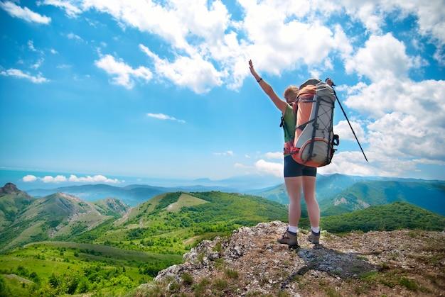 Молодая счастливая женщина с походной палкой, рюкзаком стоит на скале с поднятыми руками и смотрит на зеленый пейзаж