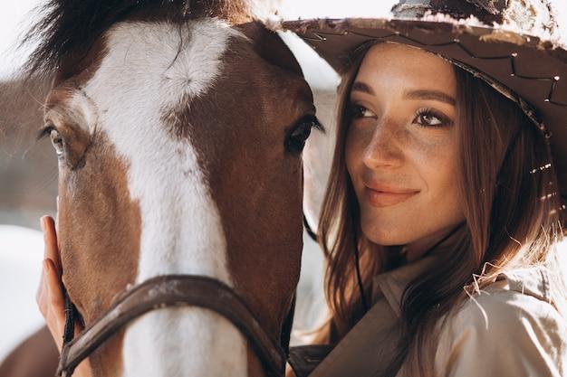 牧場で馬を持つ若い幸せな女