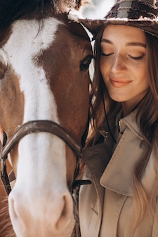 Young happy woman with horse at ranch