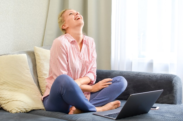Young happy woman with laptop laughing on sofa at home