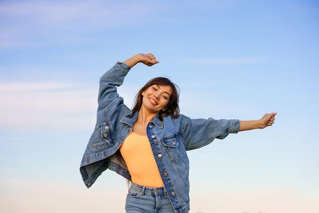 하늘을 배경으로 해변에서 춤을 추는 긴 머리를 가진 젊은 행복한 여자,