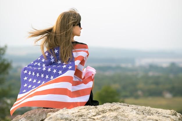 Молодая счастливая женщина с длинными волосами, держащая развевающийся на ветру американский национальный флаг на ее плечах, отдыхает на открытом воздухе, наслаждаясь теплым летним днем