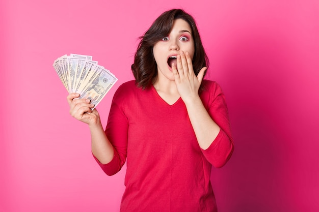 Young happy woman with money in hand, with opened mouth, looks surprised. brunette girl wins in lottery. lucky female dressed red jumper wants to spend her prize. isolated on pink.