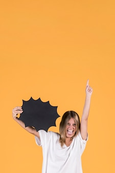 Young happy woman with mouth open holding black speech bubble and pointing up
