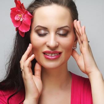 Молодая счастливая женщина с розовым цветком в волосах