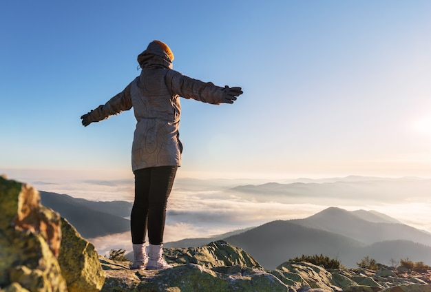 Young happy woman with raised hands on a mountain peak in low clouds looking at beautiful view at sunrise.