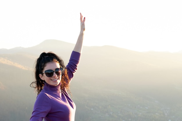 Young happy woman with raised up hand enjoying warm sunset evening in summer mountains.