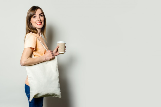 Young happy woman with a shopping bag, holds a paper cup with a coffee, looks back on a light background