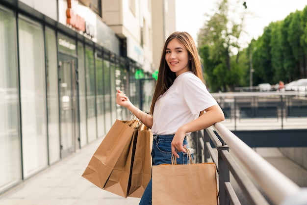 店の通りを歩いて買い物袋を持つ若い幸せな女性。
