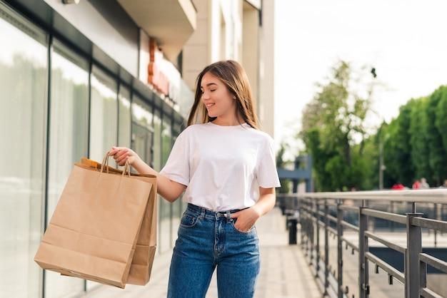 쇼핑 가방 상점 거리에 걷는 젊은 행복 한 여자.