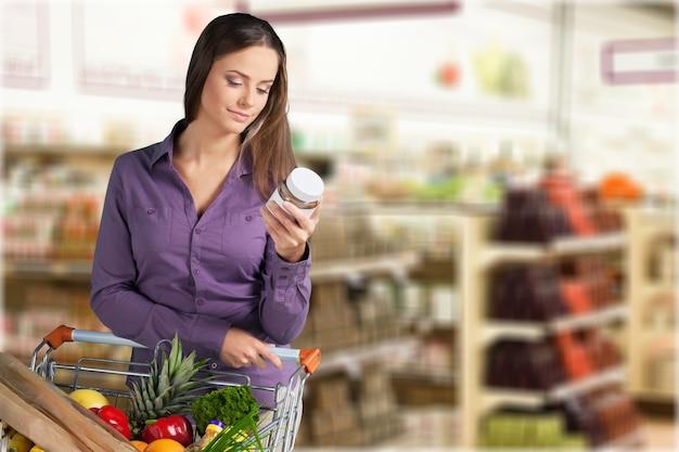 ショッピングカート、瓶を保持している若い幸せな女性