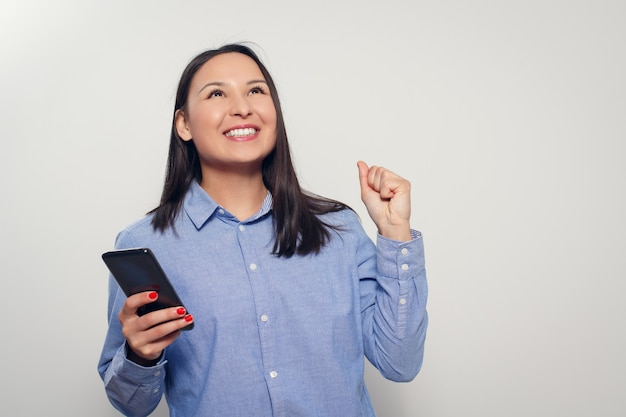 A young happy woman with a smartphone in her hand shows a gesture of success. on a white background.