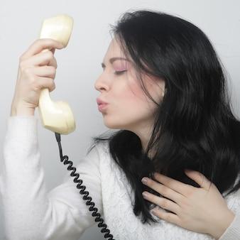 ビンテージ電話で若い幸せな女