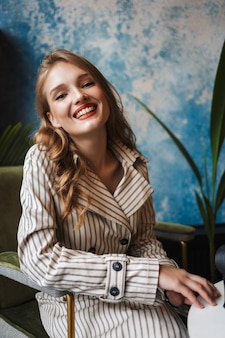 Young happy woman with wavy hair in striped trench coat joyfully