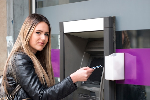 Young happy woman withdrawing money from credit card