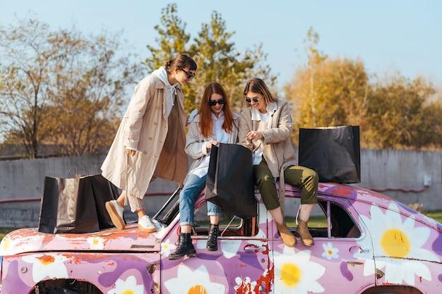 古い装飾された車に近いポーズの買い物袋を持つ若い幸せな女性
