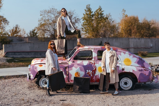 Молодые счастливые женщины с хозяйственными сумками позируют возле старого украшенного автомобиля