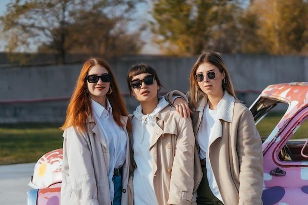 Giovani donne felici con borse della spesa in posa vicino a una vecchia automobile decorata