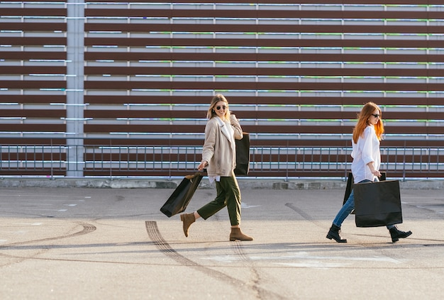 Young happy women with shopping bags walking on street.