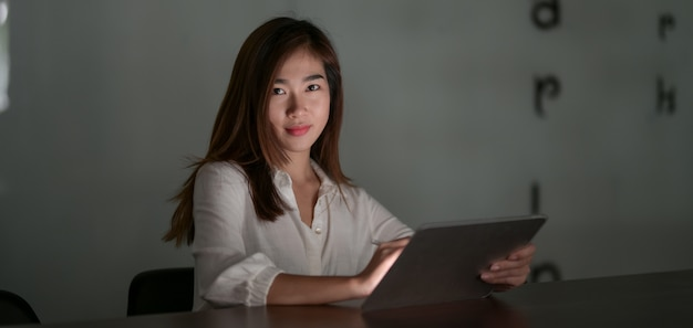 Young hard-working asian businesswoman working on her project while using tablet in modern office room at night
