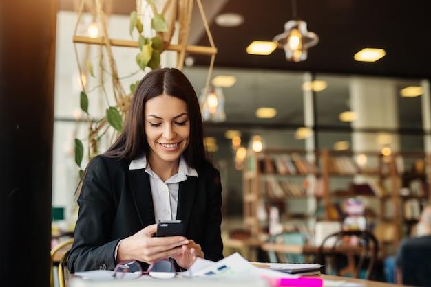 Молодая трудолюбивая мотивированная коммерсантка используя ее перерыв на чашку кофе для того чтобы закончить ее бизнес-задачи. сидеть в одиночестве в кафе и с помощью мобильного телефона.