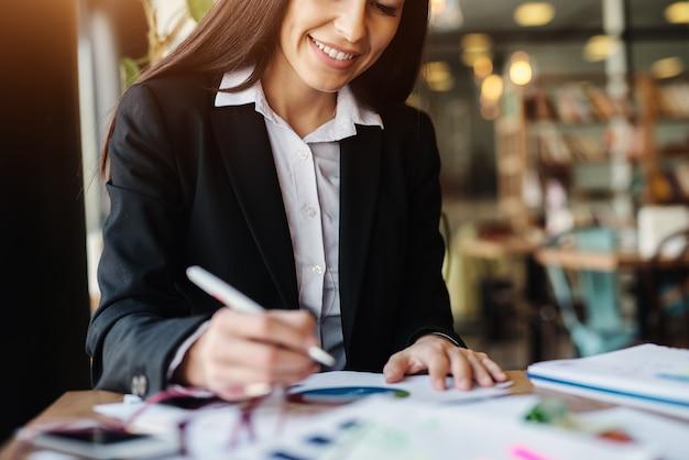 若い一生懸命やる気のある実業家は、彼女のコーヒーブレークを使用して彼女のビジネスタスクを終了します。コーヒーショップで一人で座っています。