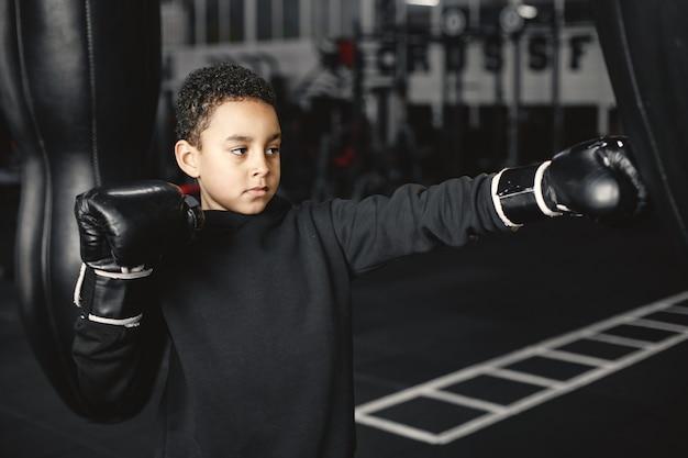Giovane pugile laborioso che impara a inscatolare. bambino al centro sportivo. kid intraprendendo un nuovo hobby