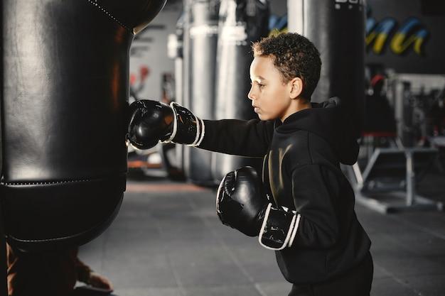상자를 배우는 젊은 근면 한 권투 선수. 스포츠 센터에서 아이. 새로운 취미를 갖는 아이 무료 사진