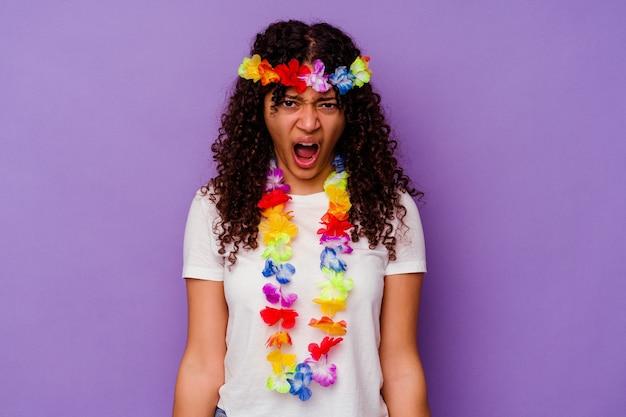 紫色の背景に孤立した若いハワイの女性は、非常に怒って攻撃的に叫んでいます。