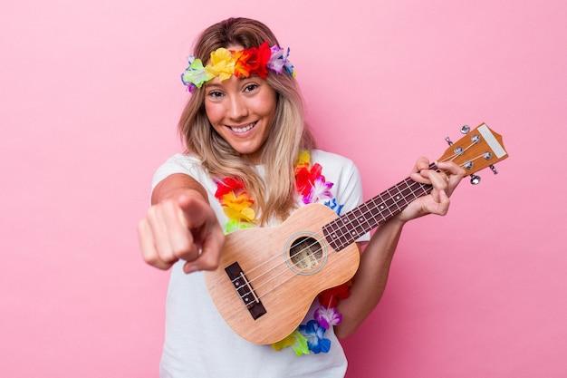 ピンクの背景に分離されたウクレレを演奏する若いハワイの女性