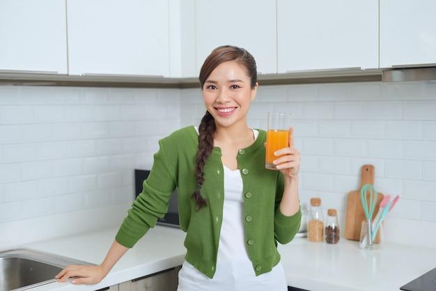 オレンジジュースを飲む若い健康なアジアの女性