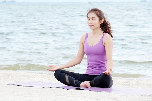 Young healthy asian woman practicing yoga on the beach
