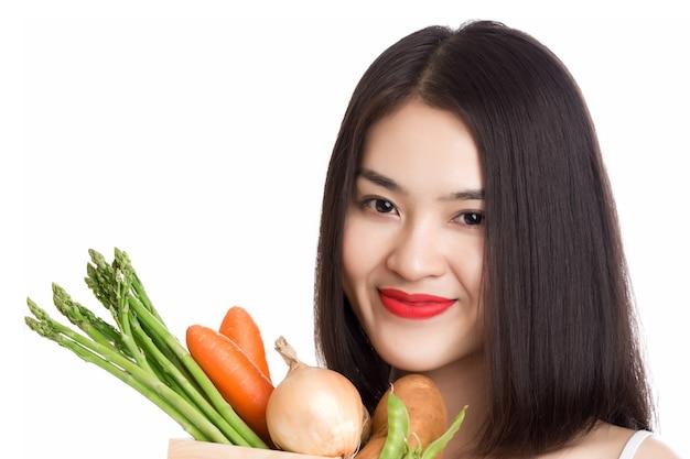 白で隔離のバスケットに新鮮な有機野菜と若い健康なアジアの女性。